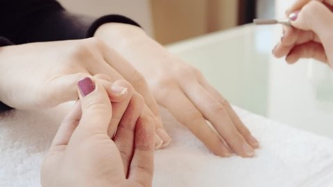 removing of cuticle in beauty salon, nail artist moves up cuticle on girl's little finger by pusher and removes cuticle by remover, manicurist uses manicure scraper tool to move up and remove cuticle