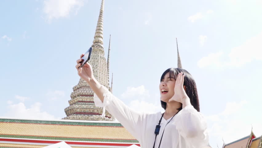 Young Asian Chinese woman tourist making video call  with smartphone while traveling in Thai temple, Bangkok Thailand