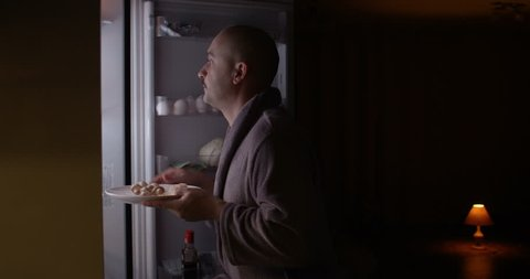 Hungry Man Looking in a Fridge Taking Plate with Food at Night Funny Behaving Shot on Red Epic