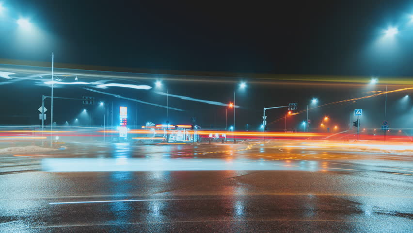 Beautiful night time lapse in Druskininkai city, Lithuania. Long exposure time lapse of fast moving cars with light trails during dark hours. Foggy city lights. | Shutterstock HD Video #1023336424