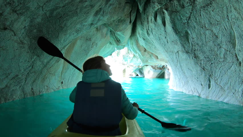 Woman paddles kayak and explores Marble Cave located near the town of Puerto Rio Tranquilo on General Carrera Lake. Chilean Patagonia