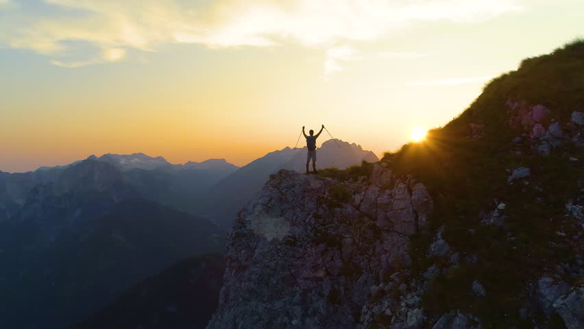 SILHOUETTE, DRONE, LENS FLARE: Golden morning sun rays shine on the ecstatic man hiking in the picturesque Slovenian Alps. Young male hiker celebrates reaching the mountaintop to see the sunrise. #1023348424