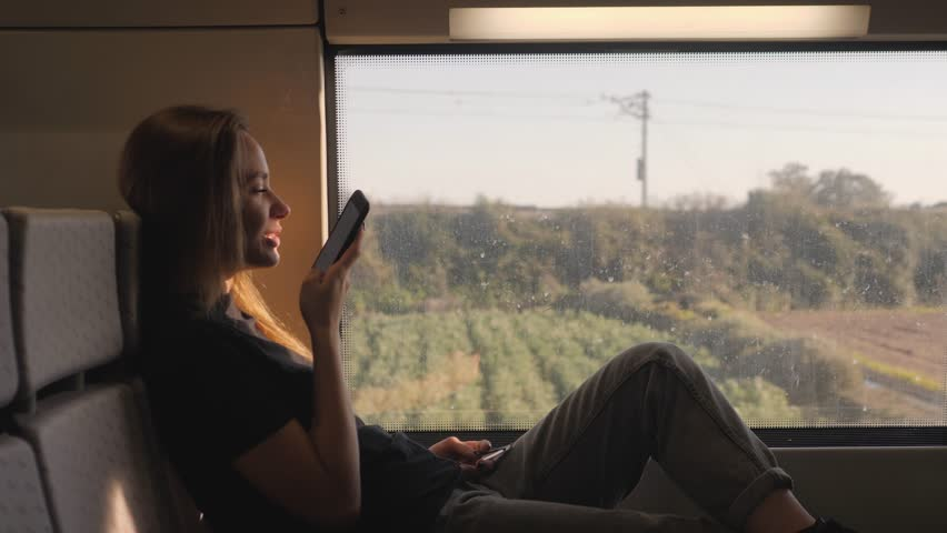 Phone voice audio message ai speech recognition. Young stylish fashion girl student woman traveling phone looking out the window while sitting in the train lookbook sun flares subway underground | Shutterstock HD Video #1023352354