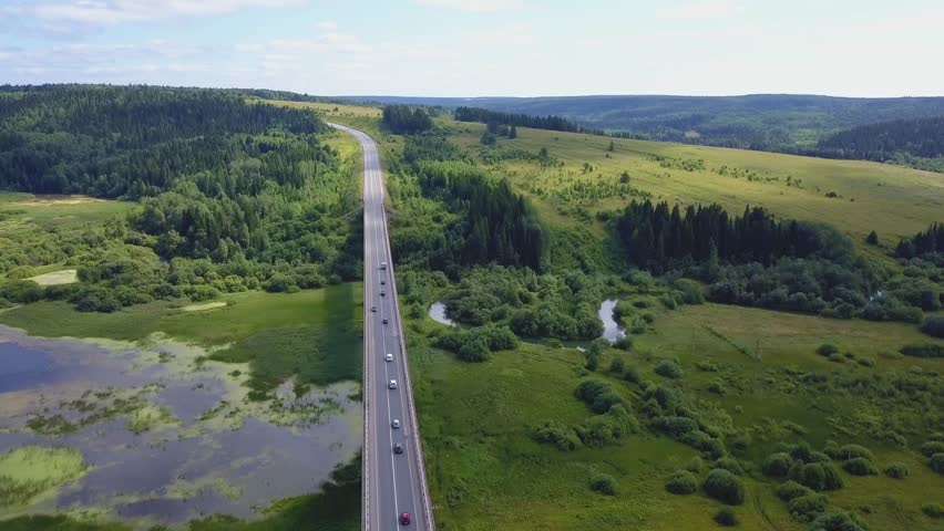 Aerial view of a busy bridge road with moving cars crossing a swamp with water and valley. Clip. Cars moving.