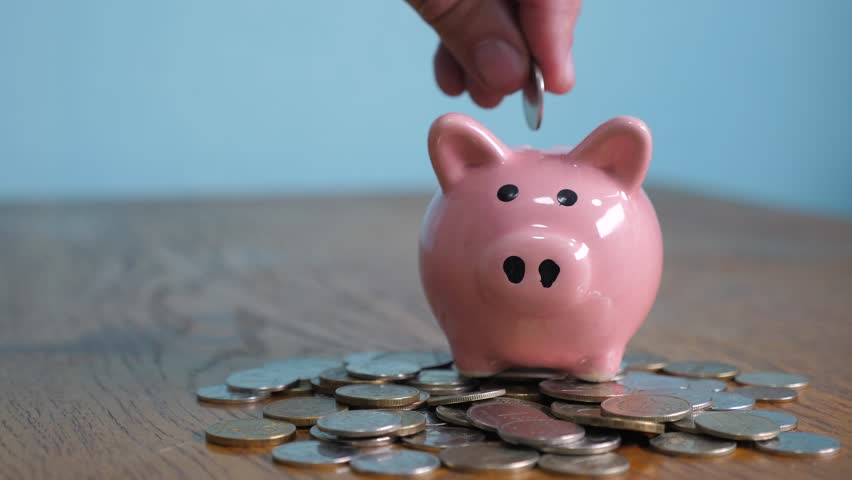 piggy bank business standing on a pile of coins concept. A hand is putting a coin in a piggy bank on a yellow background lifestyle. saving money is an investment for the future. Banking investment and