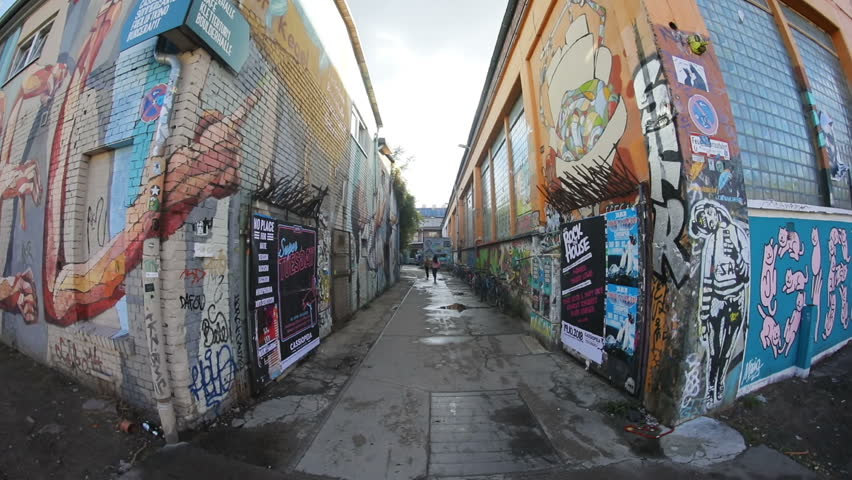 Berlin, Germany - 20 July, 2018: Alleyway with graffiti buildings. Urban concept. Contemporary art. City life. Silhouettes of young women. Bicycles. Transport. Daytime.