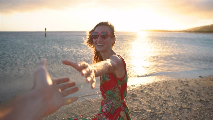 Girl leading boyfriend to the beach at sunset. Slow motion shot of woman holding lover's hands on the beach and leads him towards the sunset. Follow me concept point of view  | Shutterstock HD Video #1023411274