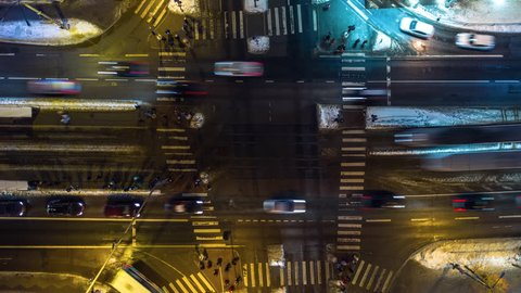 Busy intersection night aerial timelapse with pedestrians, cars, trams and buses. Aerial top-down view of an intersection with heavy rush hour city traffic