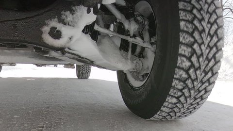 Driving plate POV of a snow tire on truck driving down the road in winter