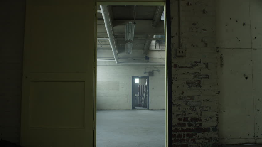 Slow move through door frame revealing a vacant and abanonded industrial loft warehouse. Filmed with RED Dragon 6K camera | Shutterstock HD Video #1023446884