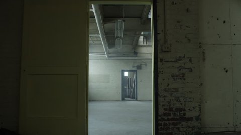 Slow move through door frame revealing a vacant and abanonded industrial loft warehouse. Filmed with RED Dragon 6K camera