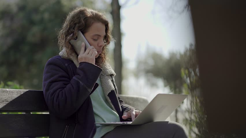 Thoughtful middle aged woman talking on smartphone outdoor. Confident businesswoman having conversation through phone while sitting on wooden bench with laptop on her knees. Technology concept | Shutterstock HD Video #1023452644