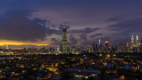 Time lapse: Beautiful and dramatic sunset view of the Kuala Lumpur city skyline from afar and high angle in Malaysia overlooking the newly built Exchange 106 Tower. Pan to right motion timelapse.