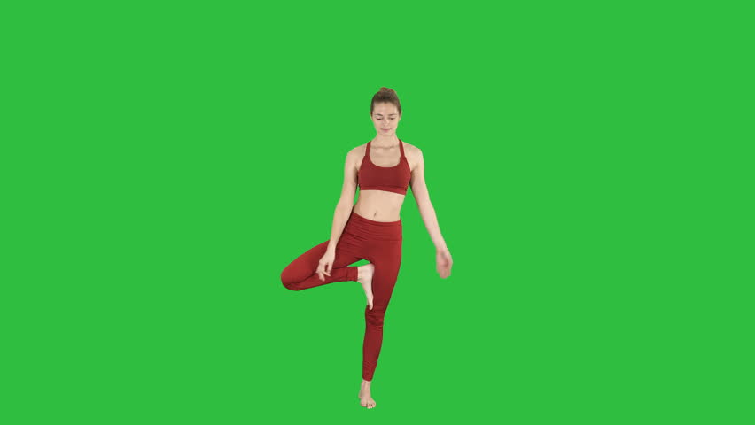 Young woman practicing yoga, standing in Utthita Hasta Padangustasana exercise, Extended Hand to Big Toe pose on a Green Screen, Chroma Key.
