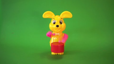 Yellow rabbit doll beats drum on green screen