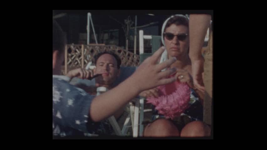 Woman puts Pink bathing cap on embarrassed unhappy little boy 1962   Shutterstock HD Video #1023520534