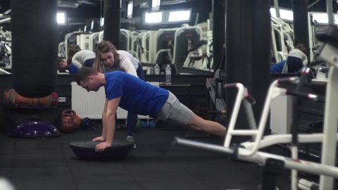 Fit instructor training unhealthy and weak male doing bosu push up at a crossfit gym for the first time
