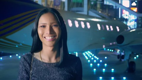 Beautiful Asian girl ladyboy looking at the camera and smiling. Thai transgender model at the airport on the background of an airplane in the evening
