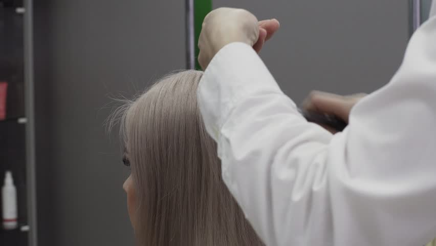 Close-up - The Hands Of A Girl Hairdresser Make Styling For Hair With Volume With The Help Of An Iron To Prepare The Wedding Hairstyle. Concept Beauty Salon And Personal Care.