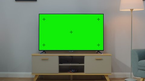 Zoom In Shot of a TV with Horizontal Green Screen Mock Up. Cozy Living Room at Day Time with a Chair and Lamps Turned On at Home.