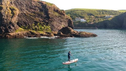 Paddleboarder moving calmly through blue waters below cliffs in Cornwall, England. The shot slowly pans to the right, showing more of the countryside beyond the cliffs