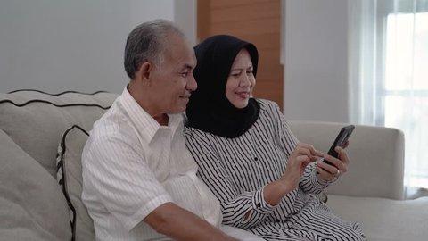 asian muslim senior couple taking selfie using smartphone at livingroom together