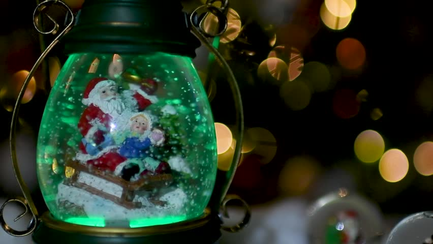 Close up of a cute snow globe with Santa Claus and child with Christmas lights blurred in the background. Flat plane