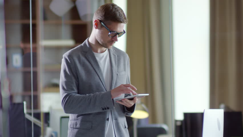 Medium shot of young businessman in glasses standing in modern office and using touchscreen of smartphone or tablet computer | Shutterstock HD Video #1023886354