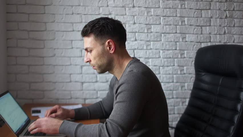 A tired young programmer in the office is working with a laptop. A man sits in a leather chair against a white brick wall
