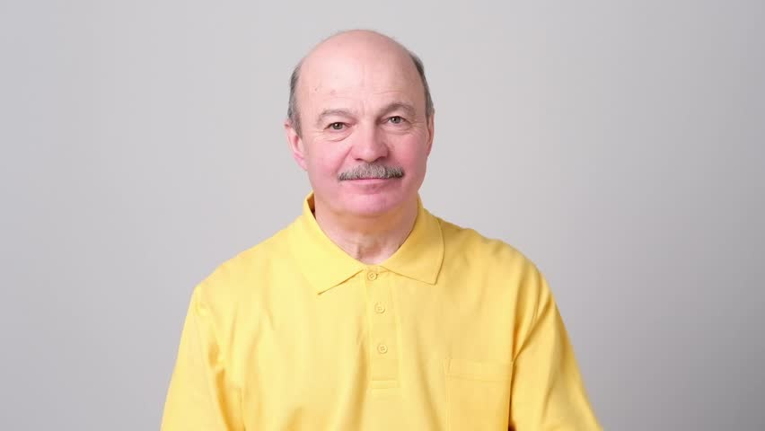 Handsome mature man in yellow shirt is showing Ok sign, looking at camera and smiling | Shutterstock HD Video #1023916324