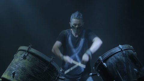 The man is playing snare drum in blue light background.