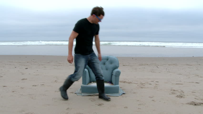 Person walks up and sits on a, not-so-typical beach chair at the Oregon Coast. | Shutterstock HD Video #10239314