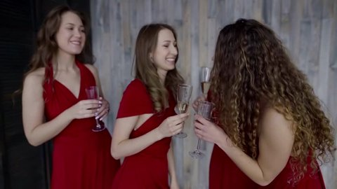 Four girl in same red dresses having fun at bachelorette party.