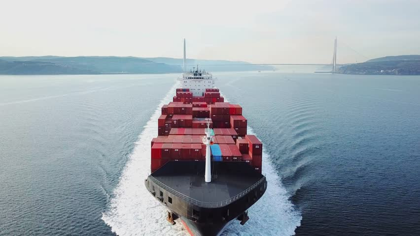 ISTANBUL - FEB 3, 2019: Low level track towards & over container ship. Aerial container ship from nose side to centre and top of frame. Shot develops from open water revealing bow and ship, to wake. C