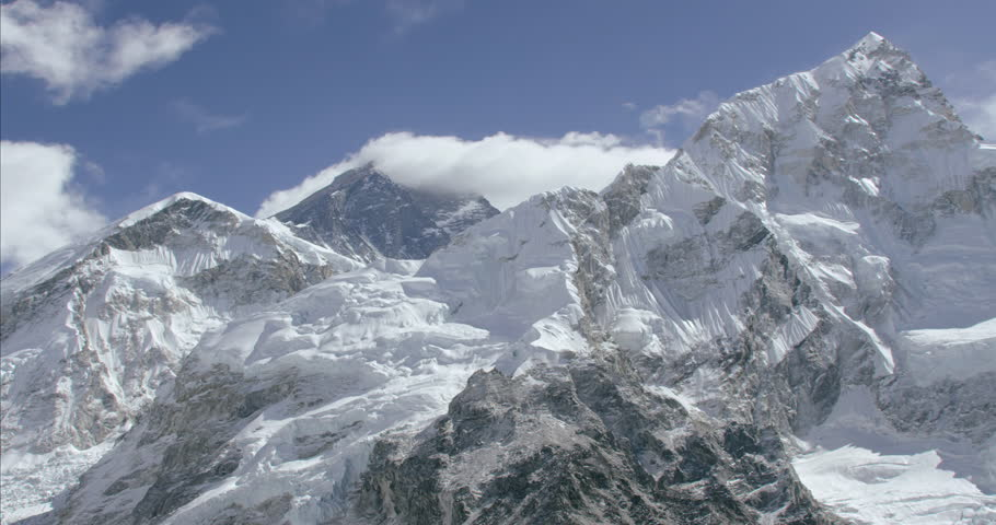 Massive rocky mountain summit peak sharp jagged cliff edge wide shot aerial POV of snowcapped ice himalayan mountains in Nepal Tibet China