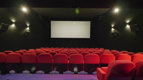 Traveling over red cinema seat row with screen in background. Movie theater smooth gimbal shot.