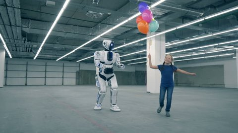 Teenage girl is dancing with balloons and walking with a human-like droid