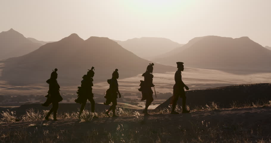 4K view of people from the Himba tribe in traditional dress, watching the sun setting on the mountains, Namib desert, Namibia | Shutterstock HD Video #1024050074