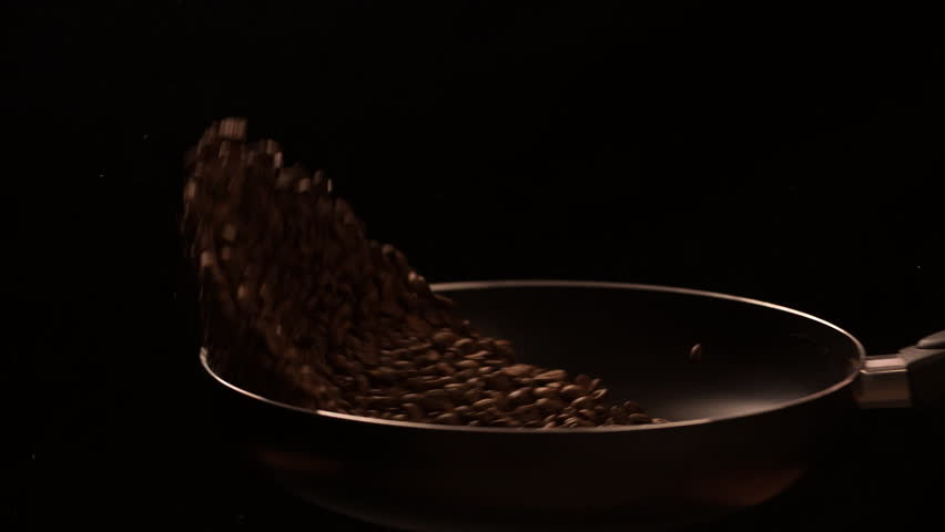Coffee beans tossing and roasting in pan cooking food slow motion video