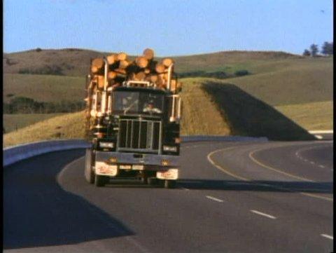 BRITISH COLUMBIA, CANADA, 1990, Logging truck drives down mountain road