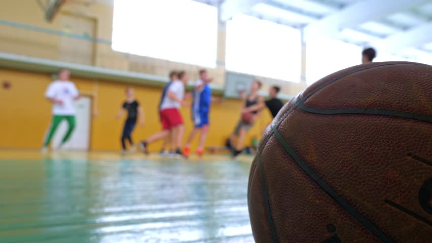 Basketball game. Teens train in the school old sports hall, throw the ball in the basket and run with the ball. | Shutterstock HD Video #1024080464
