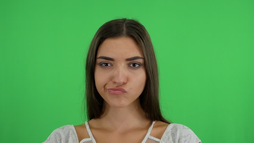 Gloomy, bored girl frowns face looking to the camera, being dissatisfied, keeps hands down, demands explanation why she looses. Angry sullen woman standing against green background. | Shutterstock HD Video #1024083374