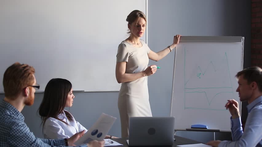 Corporate female business trainer discussing financial graph training employees group talking at team meeting, businesswoman coach mentor teaching workers at seminar giving presentation on whiteboard