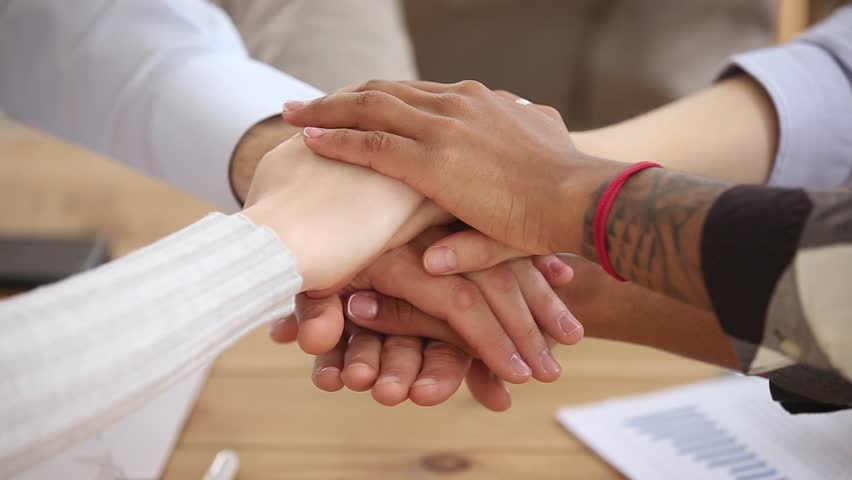 Diverse people stacking hands together in pile, multi ethnic students sales team engaged in corporate teambuilding connected in teamwork help support coaching training unity concept, close up view | Shutterstock HD Video #1024093874