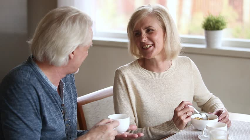 Happy middle aged mature couple talking eating breakfast drinking morning coffee together, smiling loving senior old family having fun conversation laughing enjoying brunch on date at home in cafe #1024093964