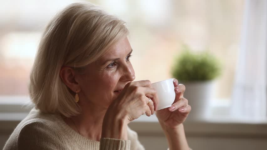 Dreamy happy middle aged mature woman looking away drinking morning coffee or tea at home, smiling senior old lady holding cup relaxing with positive thoughts dreaming enjoying pleasant memories