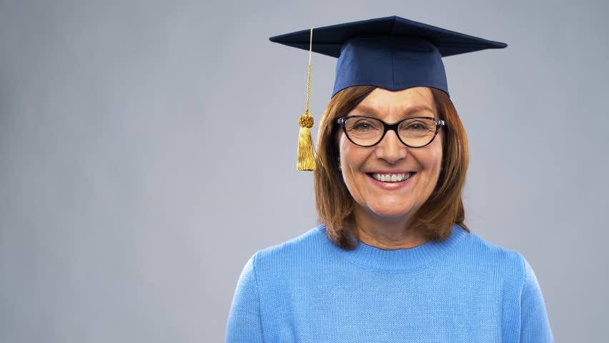 Graduation, education and old people concept - happy senior graduate student woman in mortar board showing diploma laughing over grey background | Shutterstock HD Video #1024107974