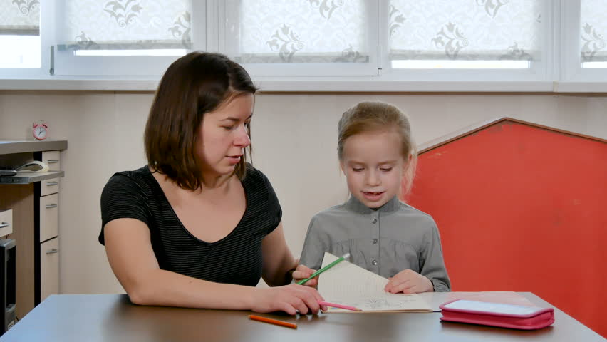 Young mother helps her daughter with her homework. study at home. Pretty girl do homework and school exercises with mom. Home education concept | Shutterstock HD Video #1024112234