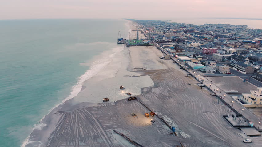 Aerial shot flying over a major dredging operation to replenish the beaches on the jersey shore after the devastation from Hurricane Sandy.