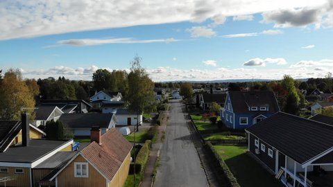 Detached houses in smaller city in Sweden. With colorful and typical Swedish and European style. The black and neutral road leading the view forward.